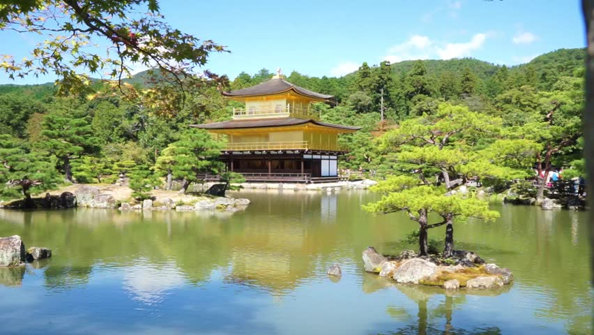 Kyoto, Japan - October 2015: The beautiful Buddhist Temple of the Golden Pavilion (kinkakuji) seen across the lake with several islands. The sunny day and blue sky make a peaceful scene.