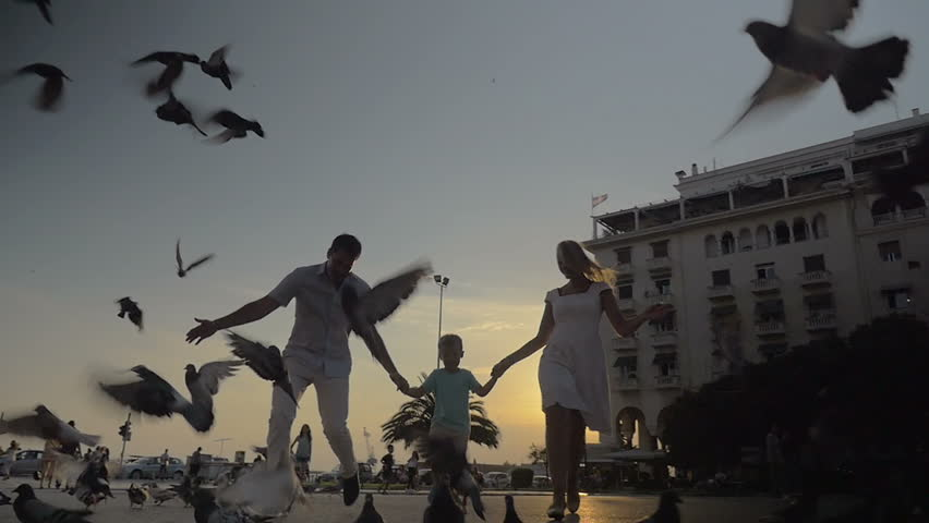 Slow motion clip of parents and little son having fun outdoor in the city at sunset. They running through the flock of pigeons eating on the ground, birds flying away