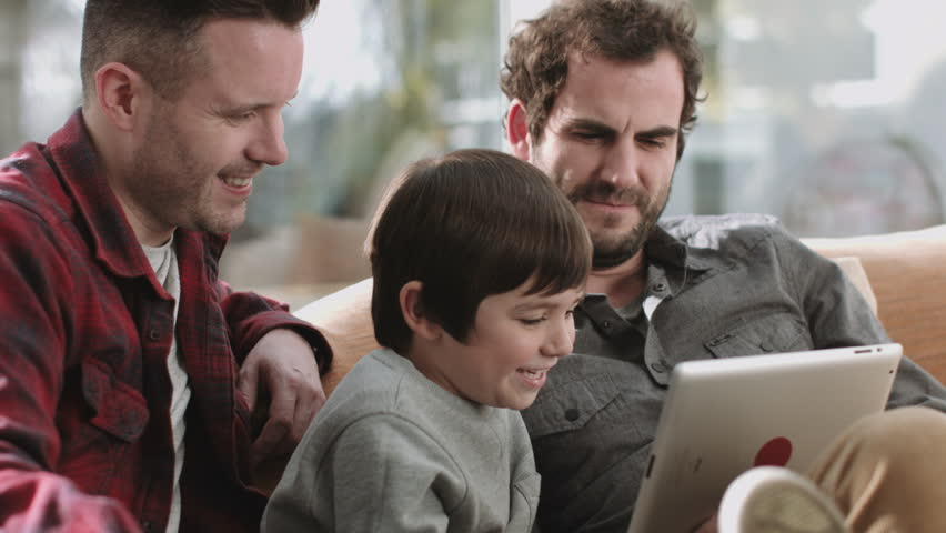 Same sex couple family on the couch using digital tablet | Shutterstock HD Video #12984443