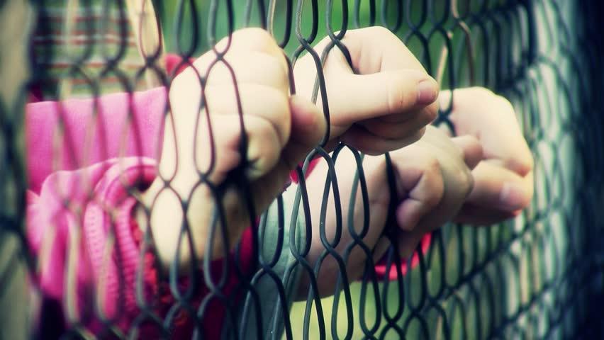 Children hands holding metal fence. Shallow DOF.