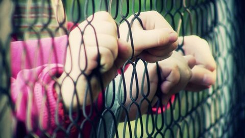 Children hands holding metal fence. Shallow DOF.