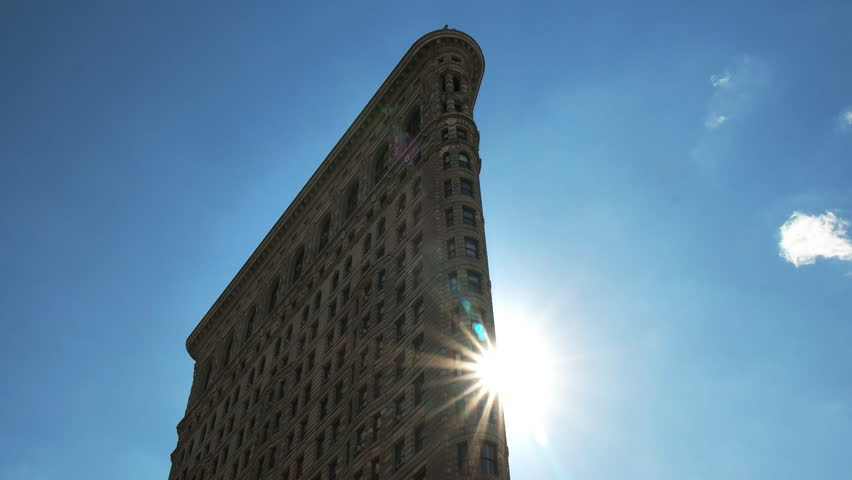 NEW YORK, NEW YORK, USA – SEPTEMBER 14, 2015: close up of the sun behind the flatiron building building in manhatten, new york