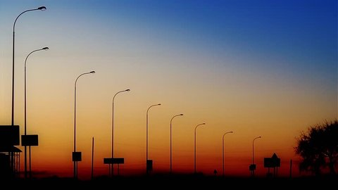 Street lights along the road turning on against twilight background