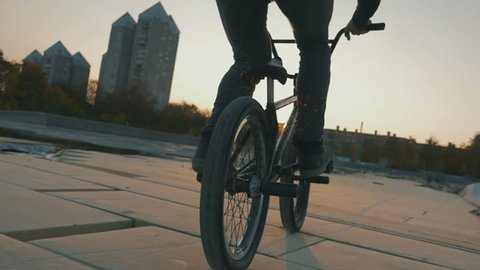 A bmx rider doing a trick in sunset in slow motion