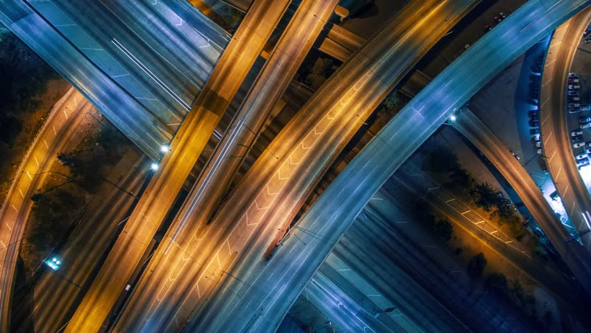 Static vertical top down aerial view of traffic on freeway interchange at night. 4K UHD timelapse background