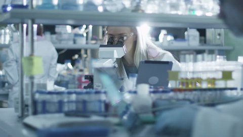 Female scientist is using a microscope and a tablet while working in a laboratory. Shot on RED Cinema Camera in 4K (UHD).