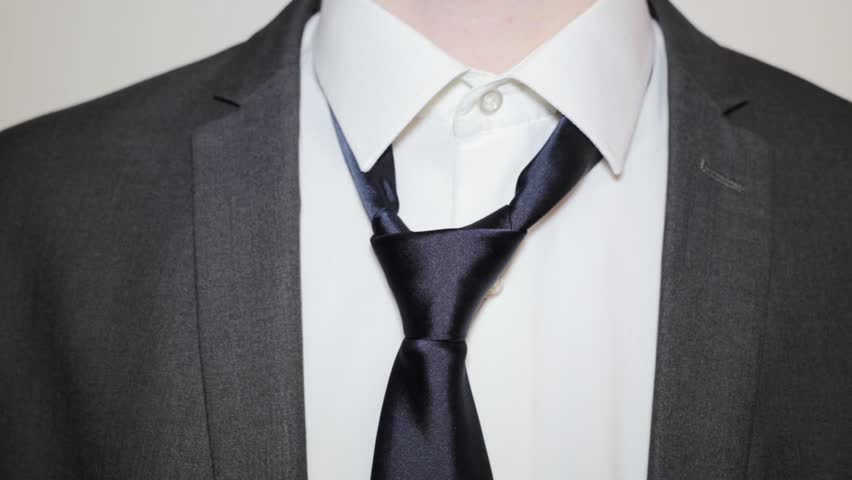 Young man in white shirt and suit tying a tie on a white background. Close-up.