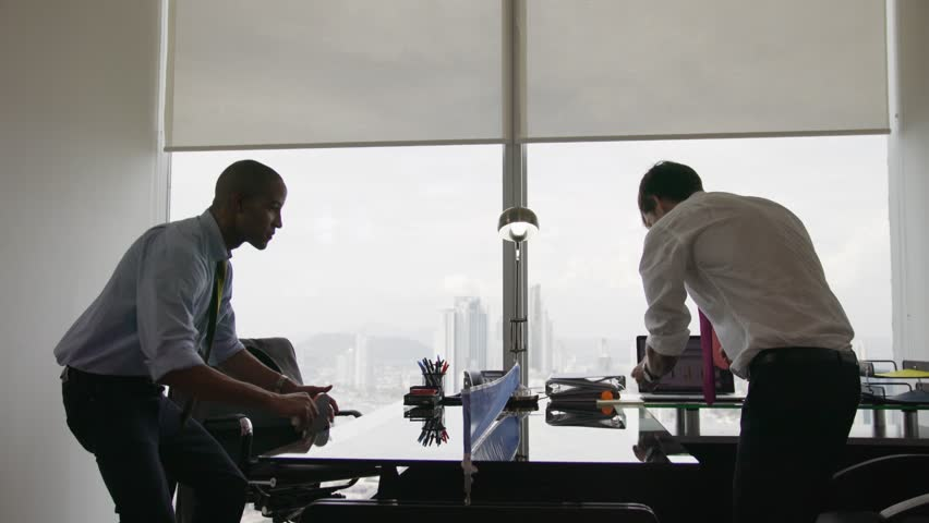 Business people doing a competition and playing a ping pong match in modern office, with sight of city and skyscrapers in background. Wide shot on dolly