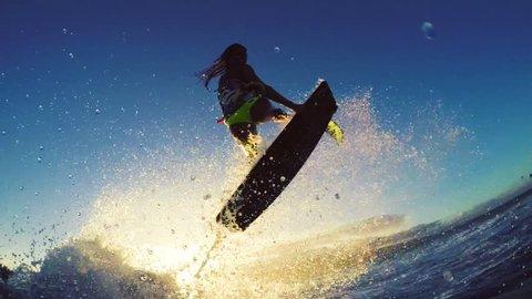 Girl Kite Surfing Catches Air Over Ocean Wave in Bikini Extreme Kitesurfing at Sunset. Summer Ocean Sport in Slow Motion.