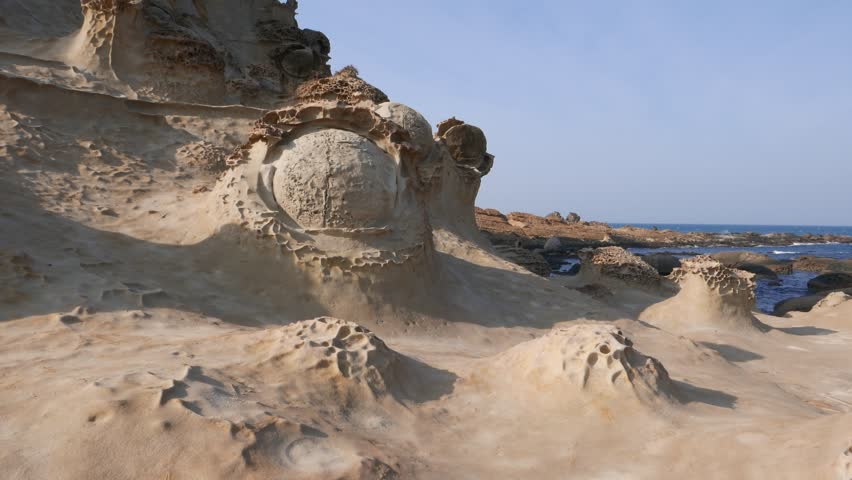Curios stone formations in Yehliu Geopark. Odd shapes of eroded rocks. Camera look on round stone like eye ball, placed against rocky cliff, pan right to sharp sandstone forms with similar pattern #13143134