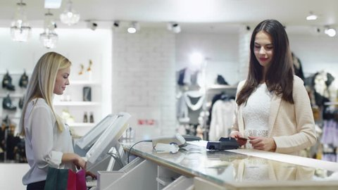 Young smiling brunette girl is paying with a card at the cash desk in a department store. Shot on RED Cinema Camera in 4K (UHD)