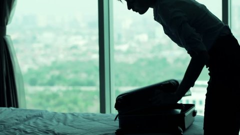 Young businesswoman packing suitcase in hotel room