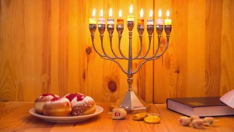 Jewish Holiday Hanukkah with Menorah (traditional Candelabra), donuts ( sufganiyot ) and wooden dreidels with glitter overlay - Track Right