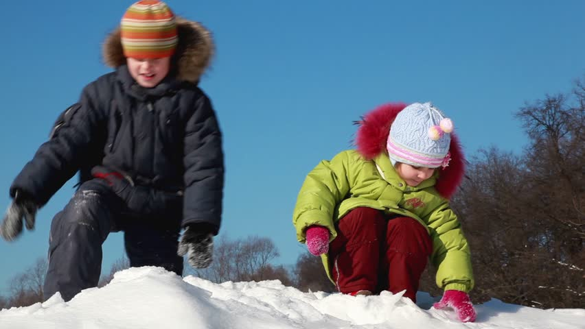 Two kids boy and girl enjoy play snowballs, girl throw snow to boys face and he become displeased, boy throw snow crust to girl and she laugh