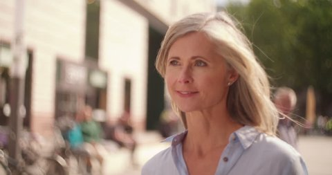 Smiling mature woman with grey hair walking confidently down a city street while holding shopping bags