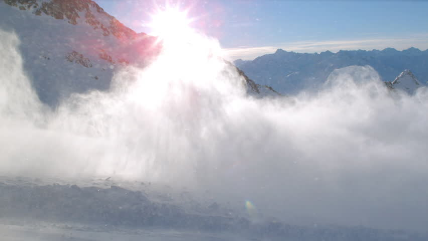 WS TS SLO MO View of snowboarder off run skiing with snowy mountains in sun ray and powdery snow / Stubai, Central Eastern Alps, Innsbruck, Austria - 01/12/2015 | Shutterstock HD Video #13197413