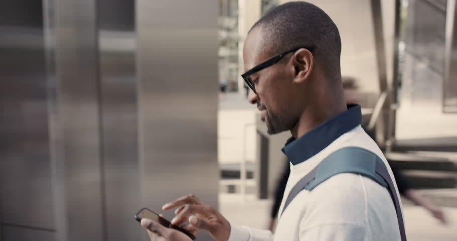 African American Man using business app on smart phone walking in city. Handsome young businessman communicating on smartphone smiling confident. Urban black male professional commuting in his 20s | Shutterstock HD Video #13200191