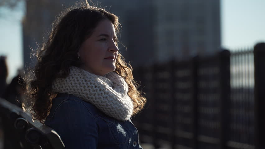 A sad woman stands contemplatively with the NYC skyline in the background. | Shutterstock HD Video #13207553