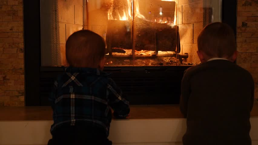 A Little Boy And Baby Sitting In Front Of A Warm And Cosy ...