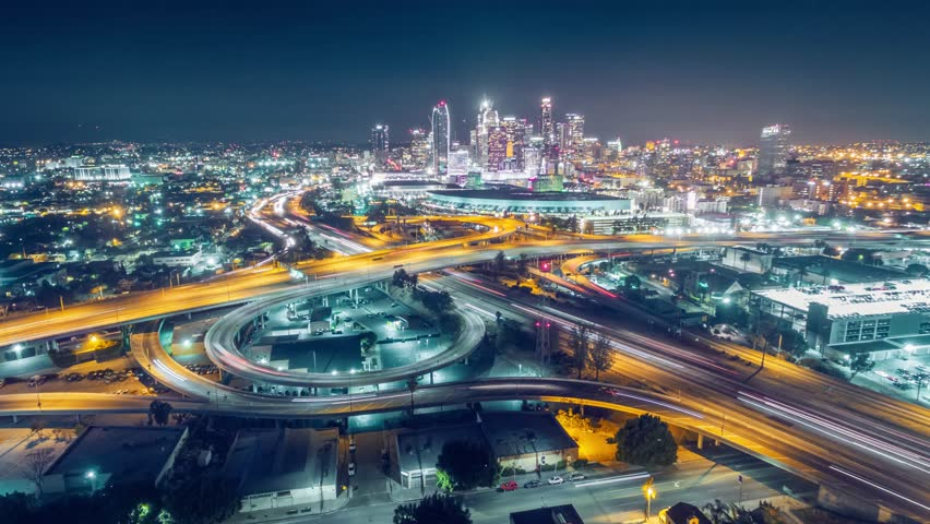Aerial view of traffic on freeway interchange in downtown Los Angeles skyline at night. 4K UHD timelapse
