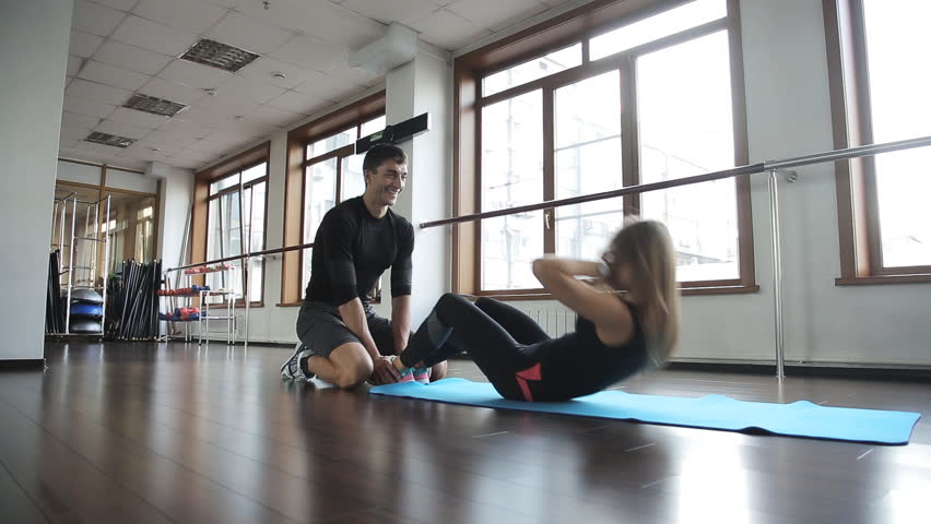 beautiful girl athlete engaged in exercises on work abdominal. Helps her in this her own personal coach with a smile on the face of fitness Caucasian man in a tracksuit, he holds her ankles
