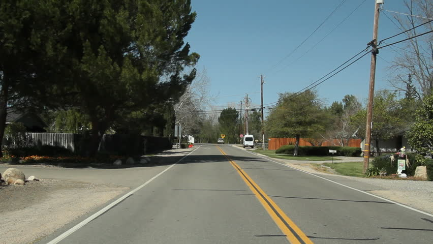 Driving plate of rural neighborhood. Back. Day with houses, trees, and blue skies. 24fps. PR 422., California, USA - May, 2010