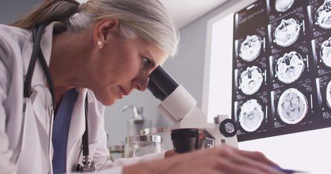 Middle aged female radiologist looking through microscope