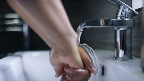4K Female hands washing under running water in a sink, in slow motion
