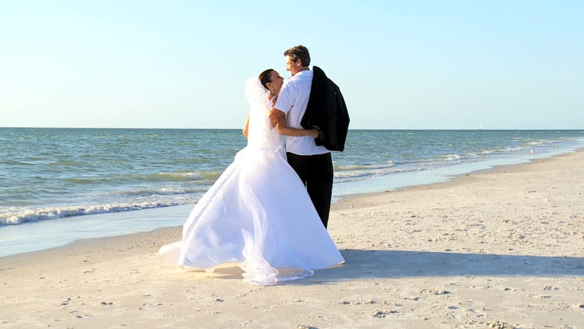 Bride & bridegroom walking on the beach after their wedding ceremony filmed at 60FPS