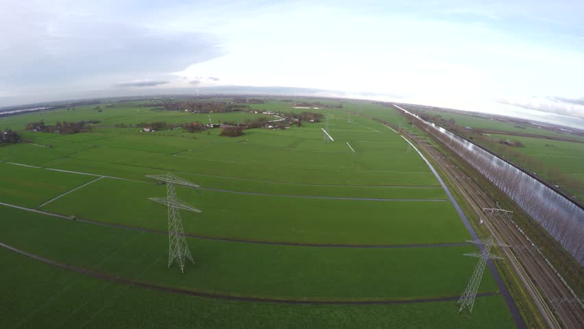 Aerial flying above transmission towers electricity pylons used for the distribution of power through steel overhead cables running in between the high iron towers green grass landscape and canal 4k