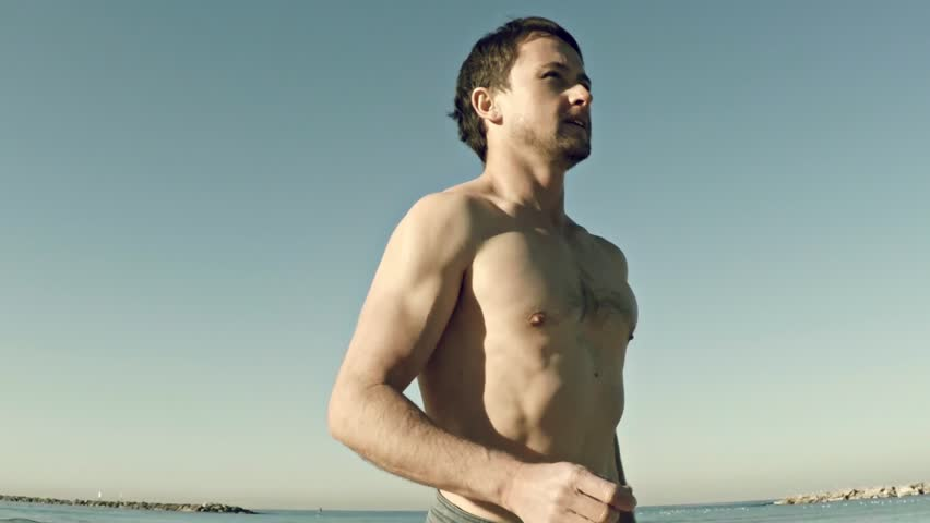 Slow Motion: Young Half Naked Man Running Along The Beach