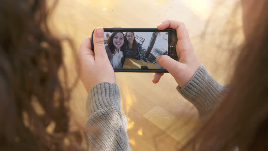 Two girls browsing through selfie pictures on a mobile phone | Shutterstock HD Video #13361843