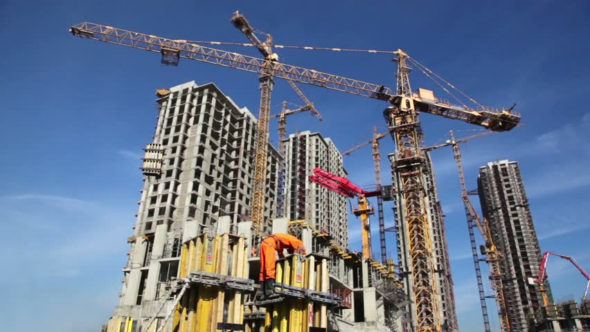Builder works at against background of the construction site high-rise buildings