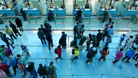 TAIPEI, TAIWAN - FEBRUARY 18, 2015: Airport immigration checkpoint counters and queue. Crowded area, people wait in line to pass immigration procedure before international flight from country.