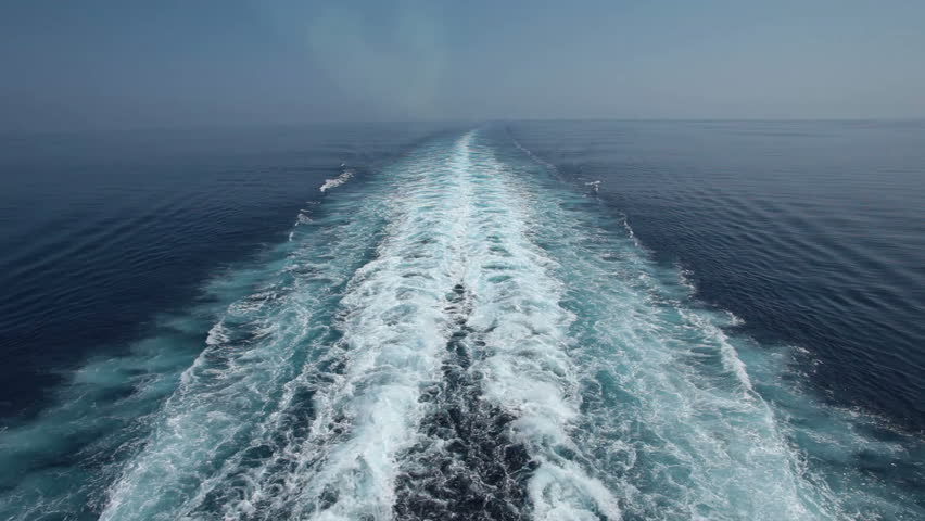Ocean and Mediterranean Sea wake behind large Cruise ship. Hazy due to pollution smoke from smoke stacks and engine. Horizon in distance.