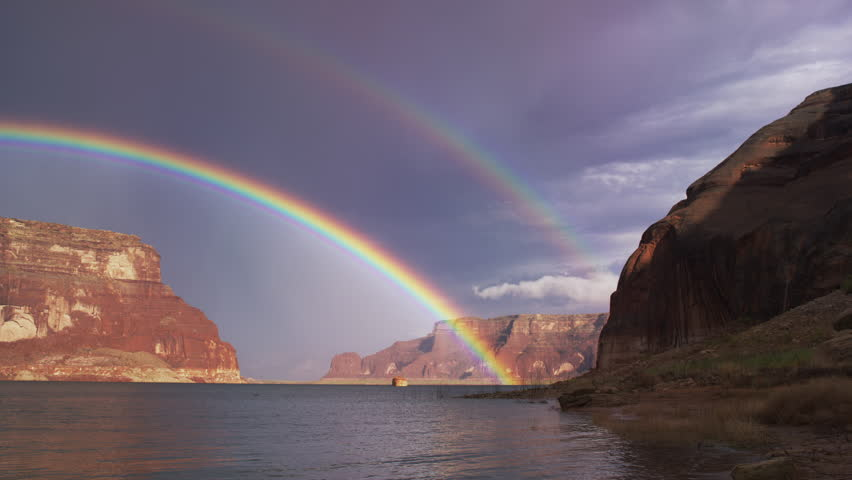 Wide shot of double rainbow over ocean / Lake Powell, Utah, United States