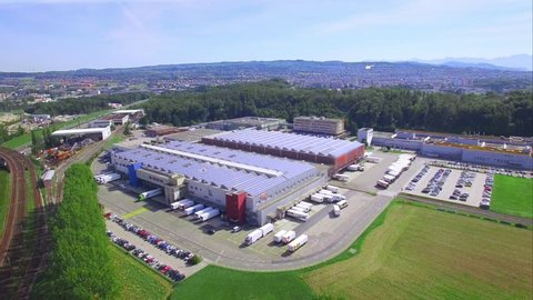 4K aerial shot - flying over a large building with solar panels / Solar energy - industrial building - green energy and sustainable development