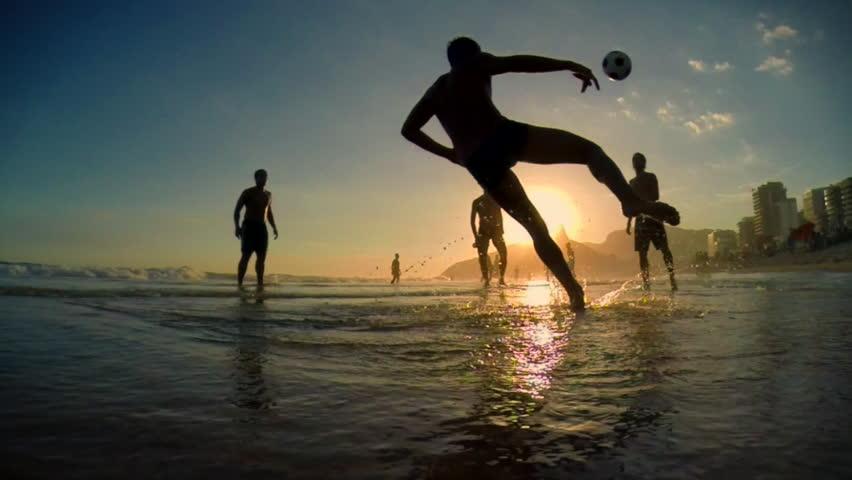 Silhouettes of carioca Brazilians playing altinho beach football at sunset on Ipanema Beach in Rio de Janeiro, Brazil