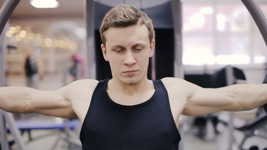 Man in gym on Pec Deck machine exercising Butterfly