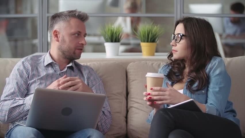 Man telling his female colleague funny jokes at coffee break   Shutterstock HD Video #13486733
