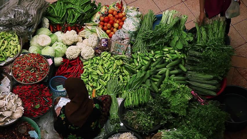 Person buys food on traditional asian market named Pasar siti khadijah in the city of Kota Bharu, Malaysia