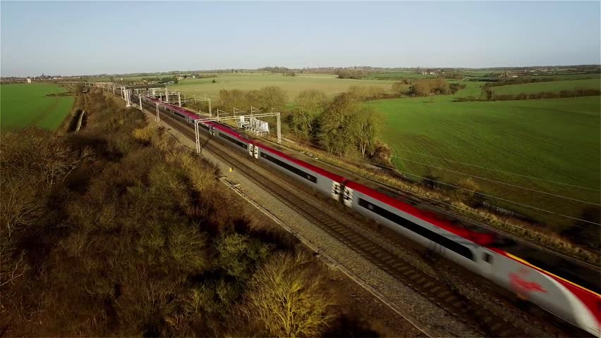 A aerial shot of a fast passenger train in the UK countryside moving towards and then passing the camera, which is tracking backwards. Plenty of cutting room either side.