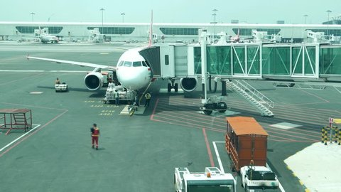 KUALA LUMPUR, MALAYSIA - MARCH 07, 2015: Aircraft approach and stop at apron, jet bridge attached, passengers go out by aerobridge, front view time lapse shot. Airliner surround by ground personnel