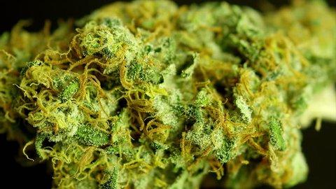 Rotating macro product shot of high quality marijuana, on a solid black background