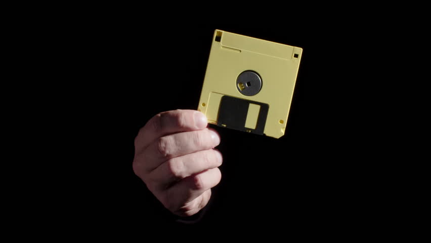 Man's hand comes out of a dark background, holding a yellow floppy disk.  Close up, repeated twice.  Originally recorded in 4K.