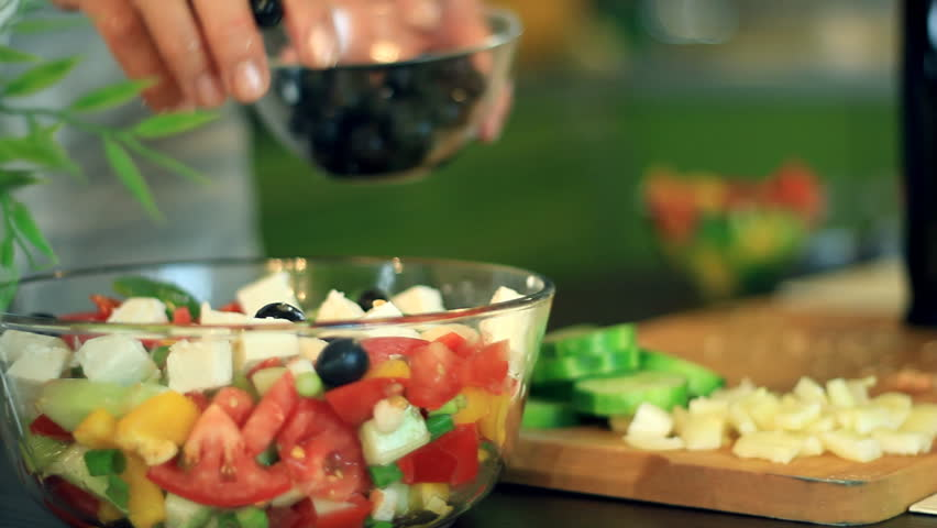 Female hands pouring oil into salad in glass bowl