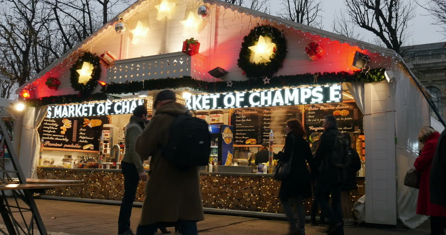 PARIS, FRANCE - CIRCA 2015: Happy people enjoying Christmas Market with diverse chalet Christmas stall selling food and mulled wine on Champs-Elysees with friends buying gluhwein mulled wine