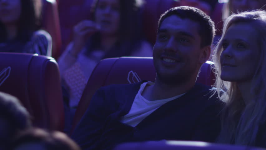 Young romantic couple is making out and kissing while watching a film screening in a movie cinema theater. Shot on RED Cinema Camera in 4K (UHD). | Shutterstock HD Video #13705751