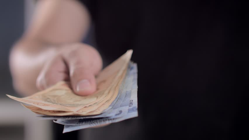 A man is telling some of Brazil banknotes to pay their bills of the month