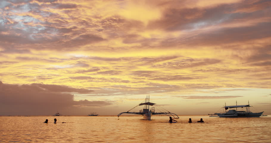 Philippines - Sunrise distant fisherman boat children playing. Sunset sunrise kids playful joy water beach clouds beautiful nature resort holiday swim play pontoon silhouette beach island paradise sun